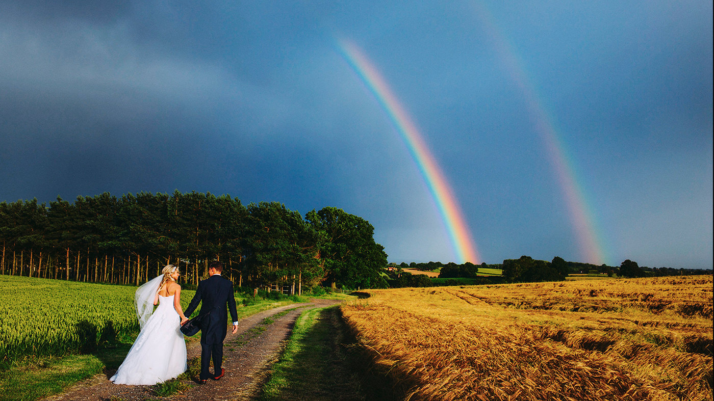Bride and grrom with double rainbow at a UK wedding
