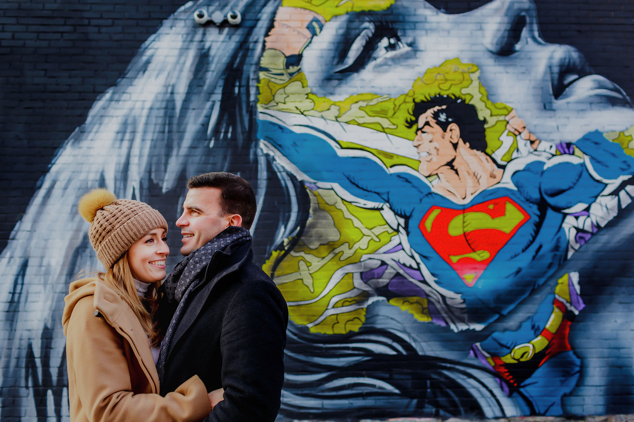 engagement photo with Superman street art in Montreal